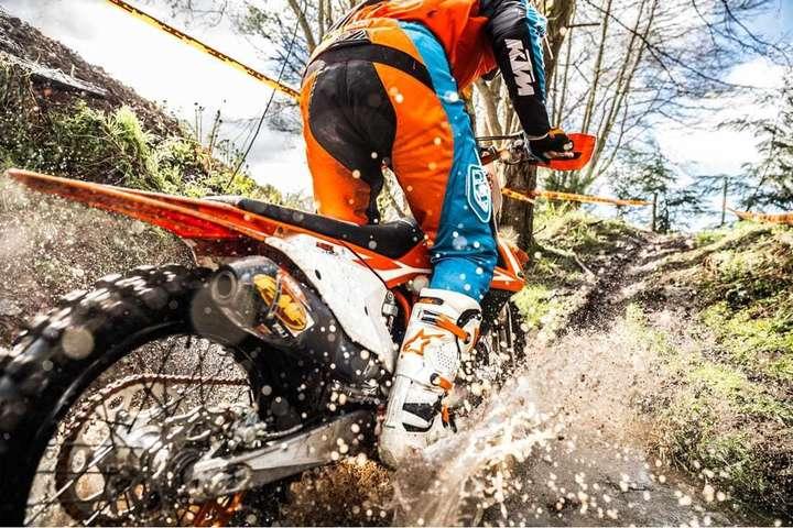 Splashing through dirt on a KTM bike